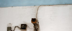 A photograph of a clunky, rusted wall-mounted surveillance camera