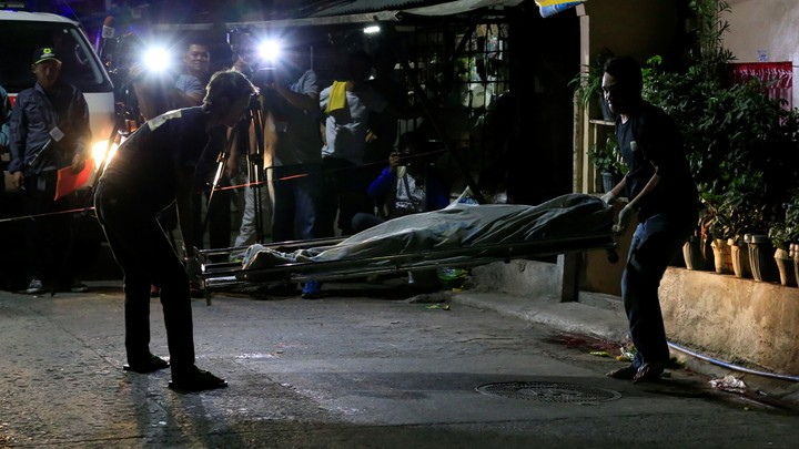 Funeral workers use a stretcher to carry the body of a suspected drug pusher.