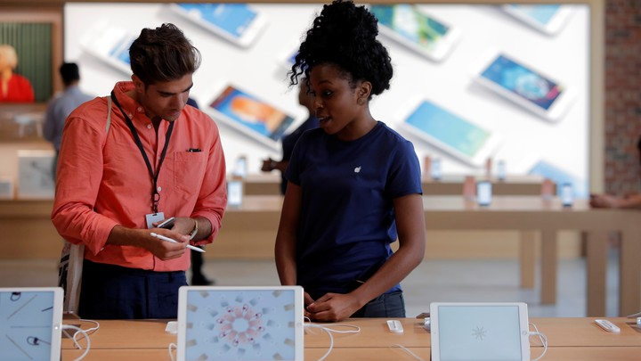 An Apple Store employee assists a customer.