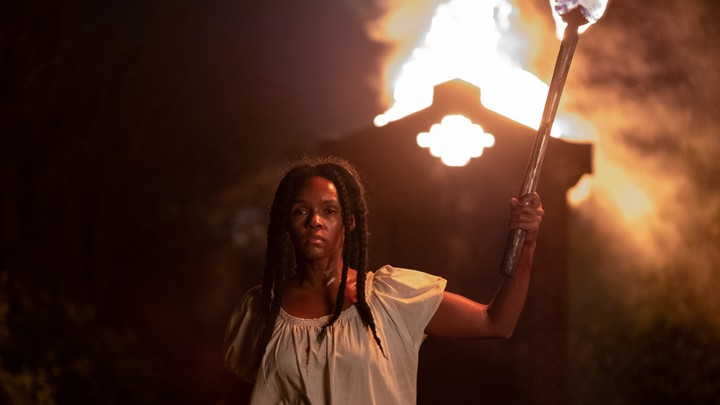 A woman holding a torch in front of a burning building