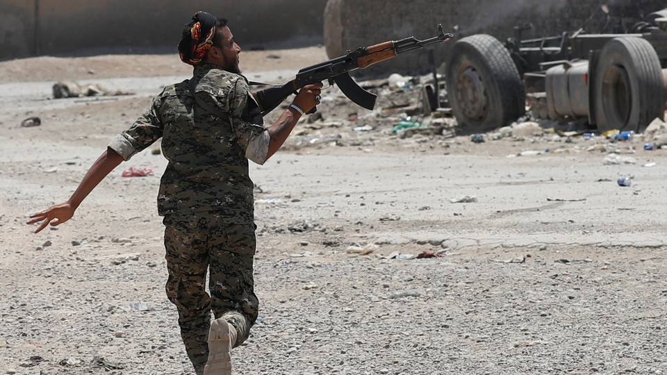A Kurdish fighter from the People's Protection Units (YPG) fires his rifle at Islamic State militants as he runs across a street in Raqqa, Syria.