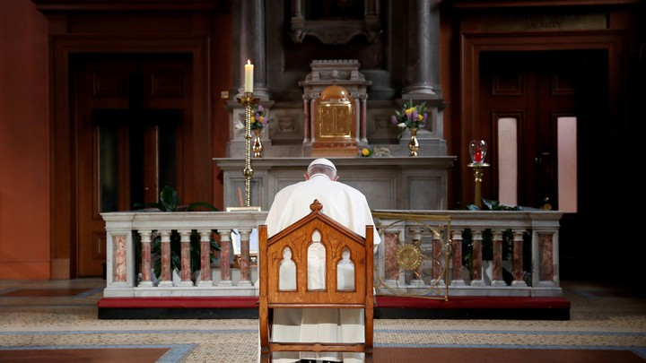 At a church in Ireland, Pope Francis sits and prays in front of a candle lit to remember victims of abuse.