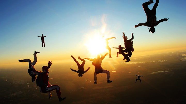 A group of skydivers pose as they fall through the air