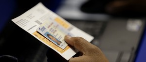 A hand holds out a voting card and a Texas driver's license