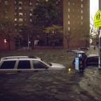 Cars submerged in a flooded street in front of an apartment building