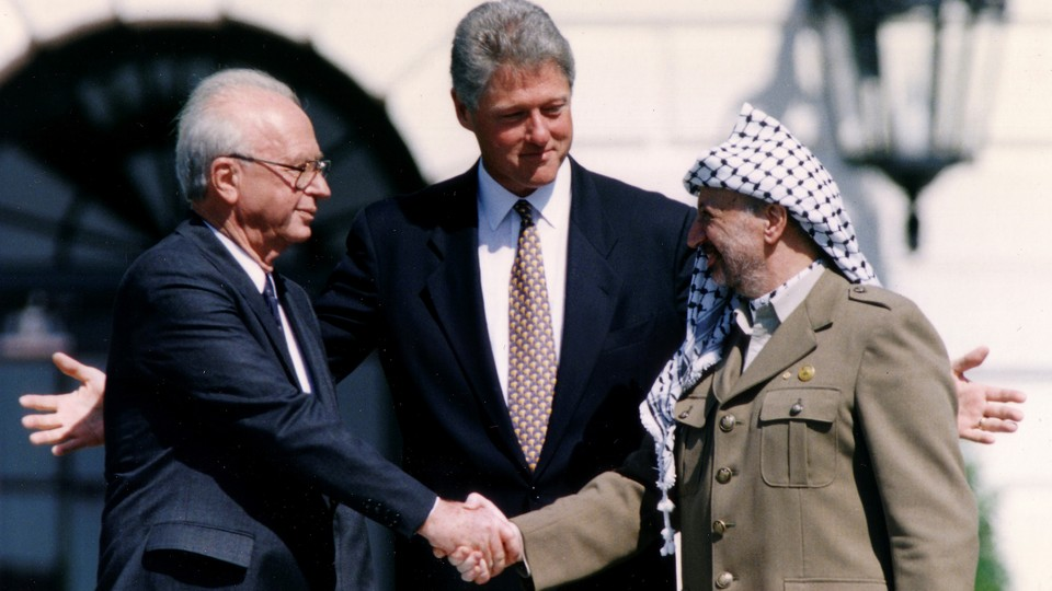 Rabin and Arafat shake hands, with Clinton behind them, on the South Lawn of the White House.