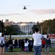 A helicopter flies over the White House as a crowd looks on