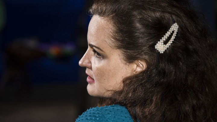 A woman with dark hair and a white hair clip watches a screen off-camera