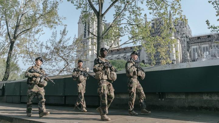 An army patrol walks along the River Seine in Paris, France.