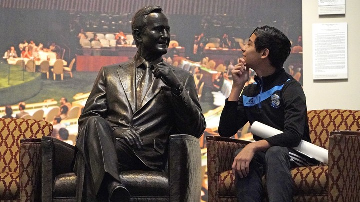 Andrew Lopez, 12, of Midland, Texas, next to a statue of George H. W. Bush inside the George H. W. Bush Presidential Library and Museum