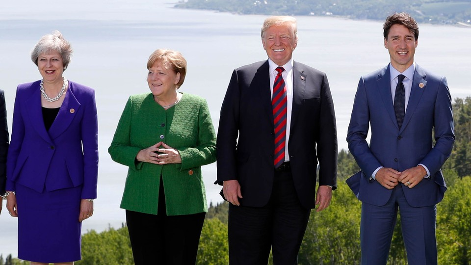 Theresa May, Angela Merkel, Donald Trump, and Justin Trudeau pose during a family photo at the G7 summit in the Charlevoix city of La Malbaie