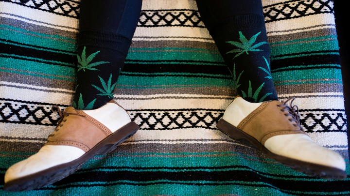 The legs of a person who is wearing socks that feature marijuana leaves