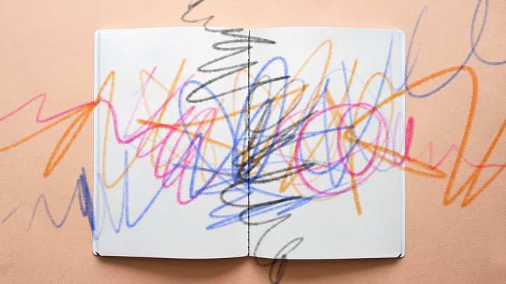 A coloring book covered in multicolor scribbles, as if from crayons