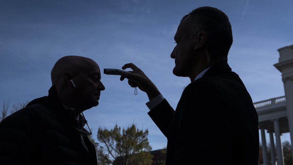 A journalist having his temperature checked by a White House staffer, both shrouded in shadow