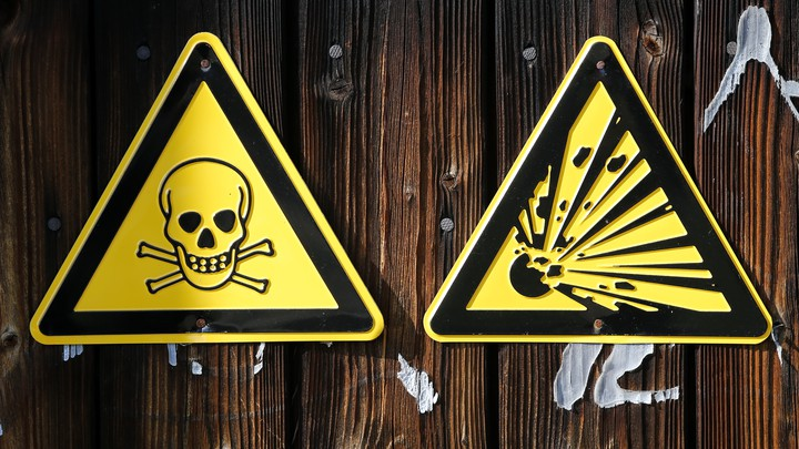 Warning signs hang on a wall at chemical weapons destruction site at the Society for the Disposal of Chemical Weapons and Ordnance .