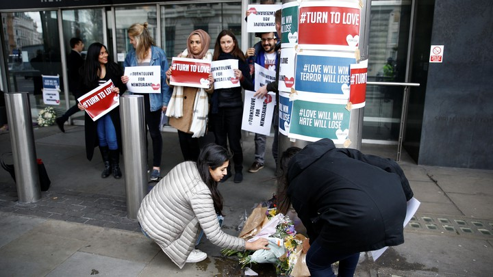 People lay flowers outside the New Zealand House following the Christchurch mosque attacks.