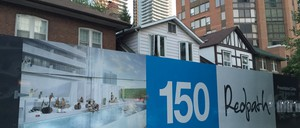 A block of older low density housing in Toronto in front of modern apartment towers.