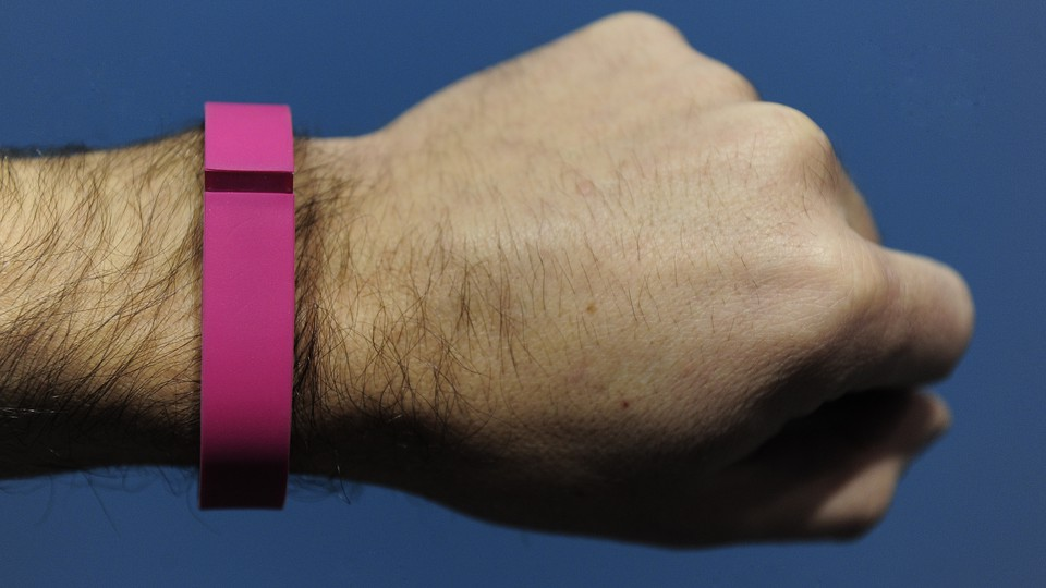 A person's arm with a fitness tracker on their wrist