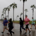 People run across the street during Hurricane Harvey