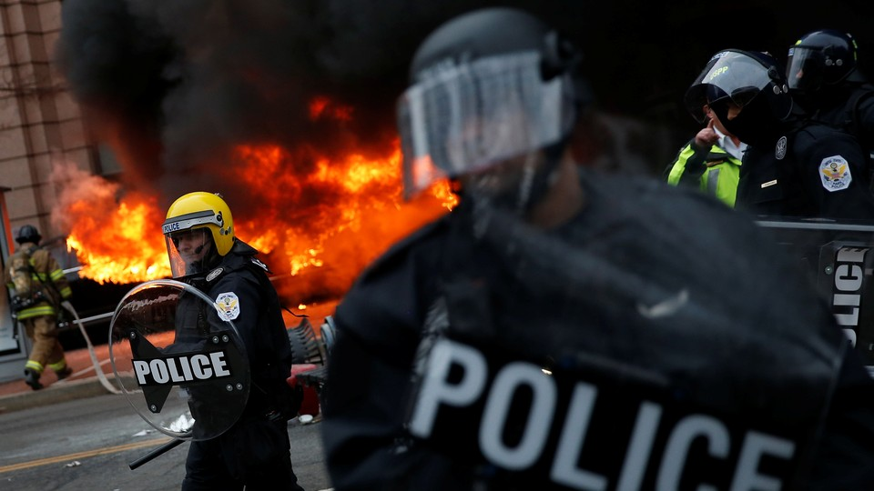 Firefighters arrive as police stand guard in front of a limousine which was set ablaze during a protest against President Donald Trump on January 20, 2017, in Washington, D.C.