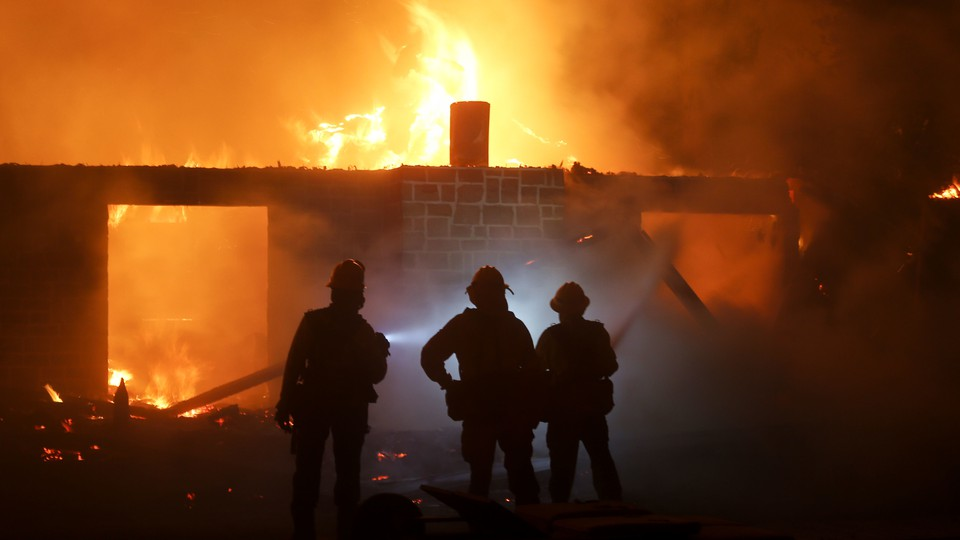 Firefighters stand in front of a burning house.