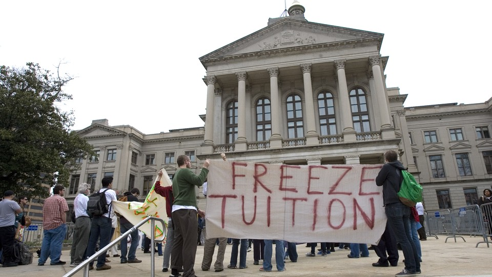 """Students and alumni hold a sign that reads """"Freeze Tuition."""""""