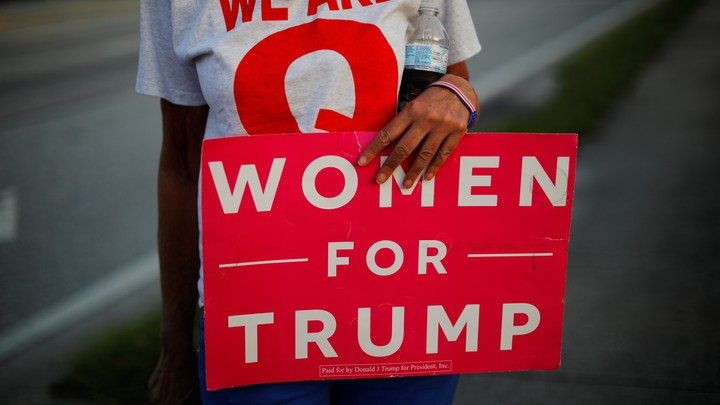"A woman holding a ""Woman for Trump"" sign."