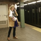 a photo of a woman covering her ears on a noisy NYC subway platform