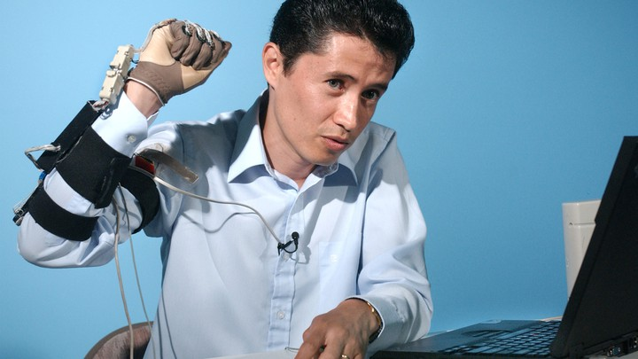 A man raises his hand, which is covered in a glove and wires