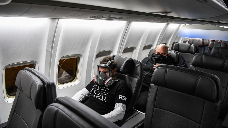 A man wears a gas mask as he travels on a flight from Miami to Atlanta on April 23, 2020.