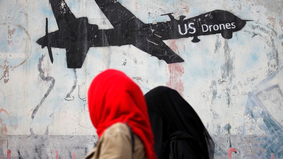 Women walk past a graffiti, denouncing strikes by U.S. drones in Yemen, painted on a wall in Sanaa, Yemen on February 6, 2017.