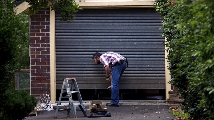 A man closes a garage door by hand.