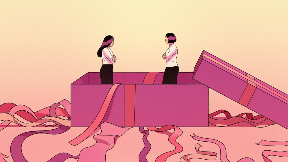 Two women look at each other while standing inside a giant present