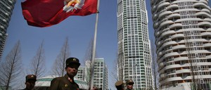 North Korean soldiers carry the Korean People's Army flag as they walk past residential buildings along Ryomyong Street in Pyongyang.