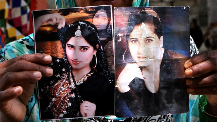 A family member holds pictures ofsinger and Internet celebrityQandeel Baloch, who was killed in July in an honor killingallegedly committed by her brother.