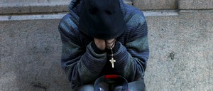A homeless man sits along a sidewalk on East 42nd Street in the Manhattan borough of New York.
