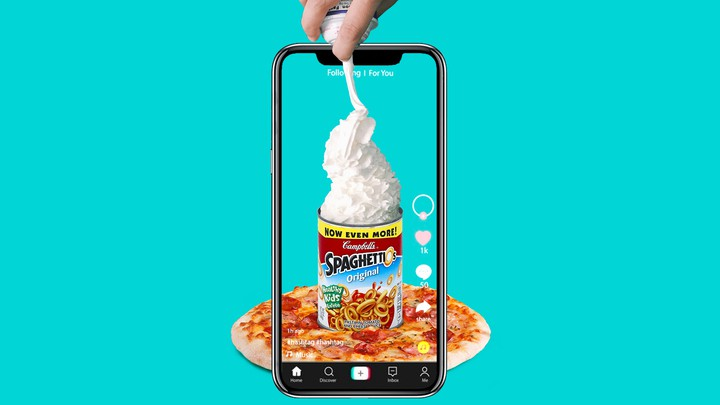A phone records a hand spraying whipped cream into a can of Spaghetti-Os on top of a pizza.