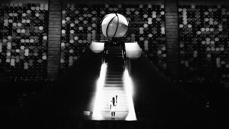 Black and white image of Japanese tennis player Naomi Osaka holding the Olympic Torch after lighting the flame of hope during the opening ceremony.
