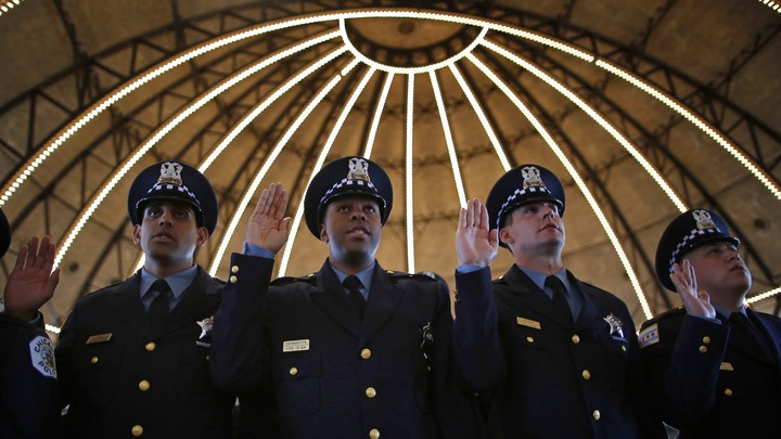 Chicago Police officers line up to be presented their certificates during the graduation ceremony for the Department's newest recruits in Chicago, Illinois, April 21, 2014.