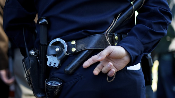 A police officer stands with one hand behind his back, with his handcuffs, flashlight, and radio visible.