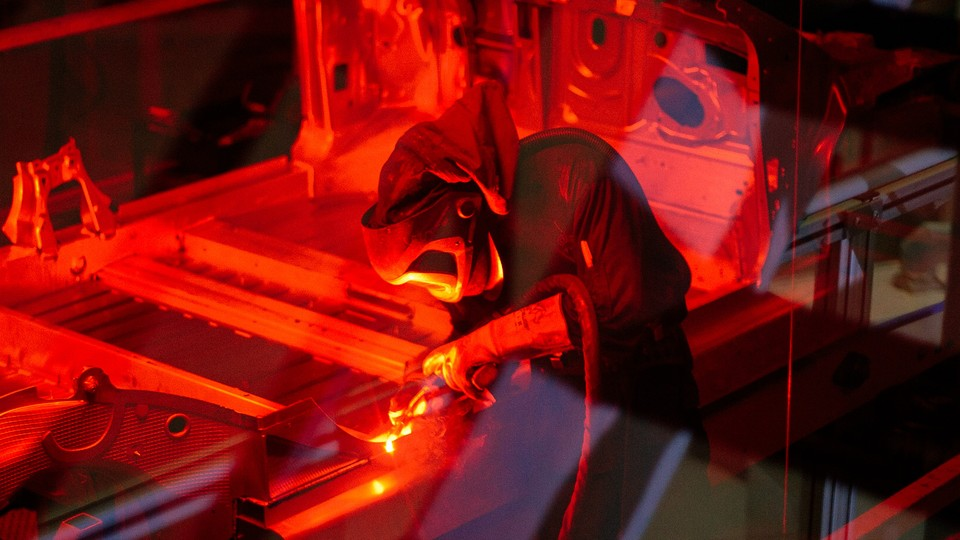 a welder works on a Tesla Model S in the Fremont, California, facility