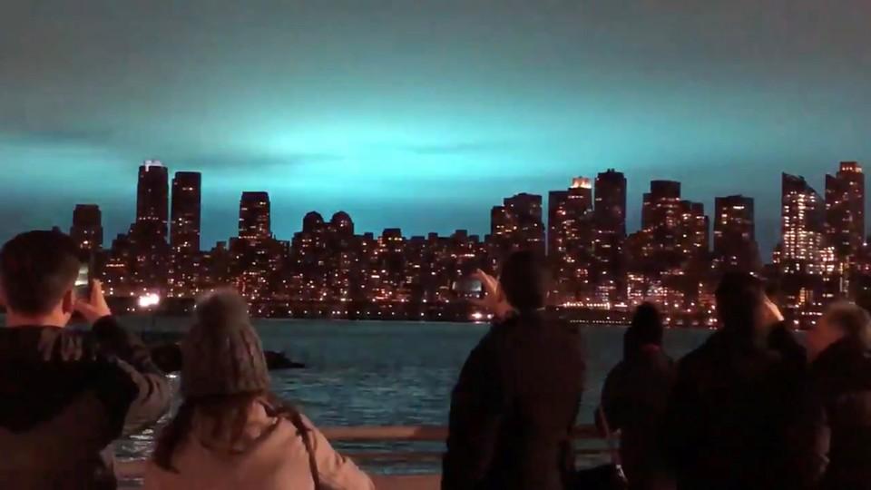 Blue light illuminates the night sky over New York City after a transformer explosion.