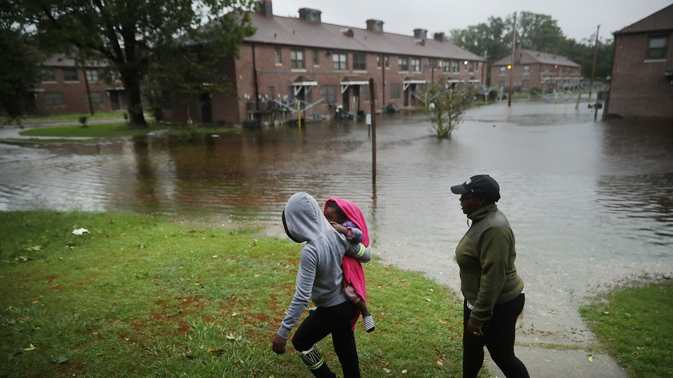 Two adults and a small child walk across a lawn with a flooded street in New Bern, North Carolina, behind them.