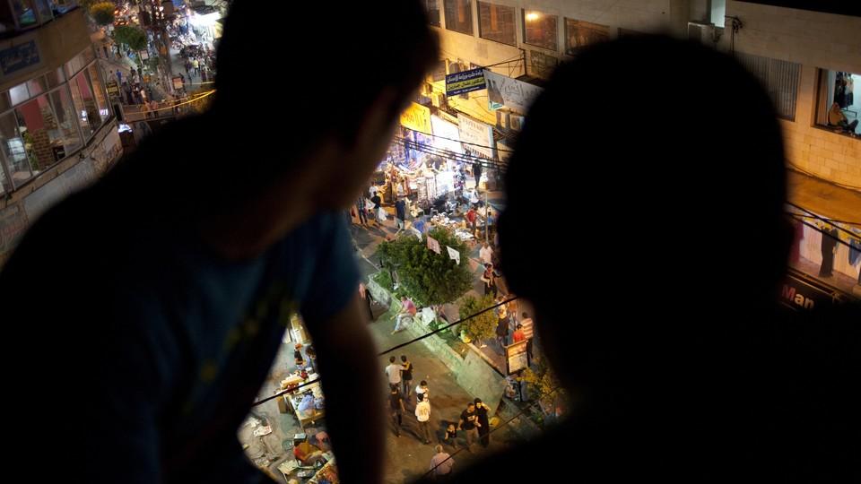 Two people watching a street below.