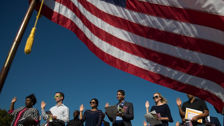 Framed by an American flag, immigrants raise their right hands and take the oath of allegiance during a naturalization ceremony.
