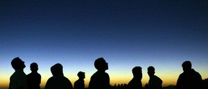 Silhouettes of people looking up at the night sky during a solar eclipse