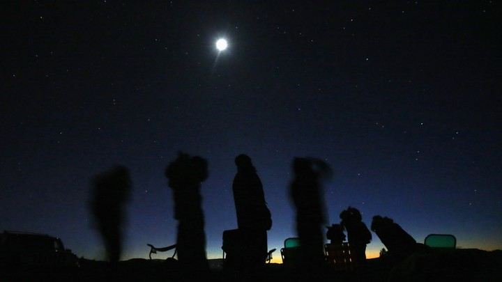 Silhouettes of stargazers against a night sky