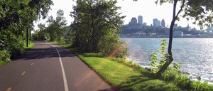 A bike path surrounded by trees facing a river and the Quebec City skyline