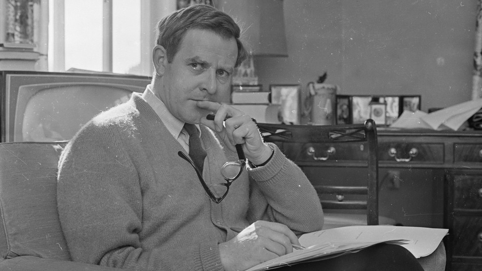John le Carré is pictured sitting at an armchair with a notepad on his lap in March 1965.