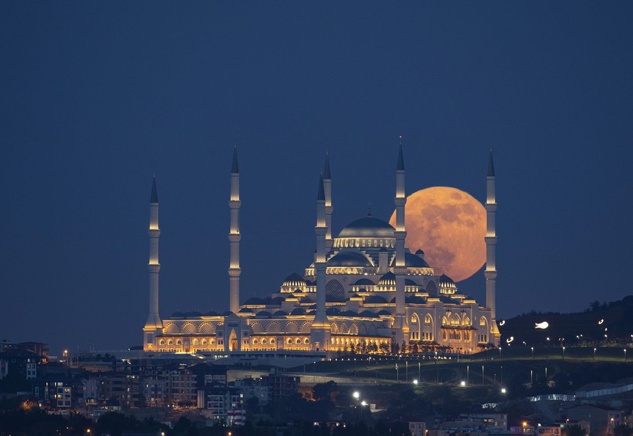 The full moon is seen behind a large mosque.